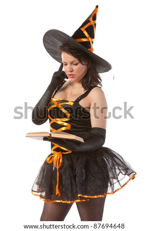 Halloween witch reads magic book
