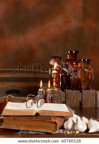 Halloween witch's kitchen with poison bottles and books - stock photo