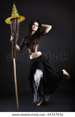 Halloween witch with a broom over black  background.