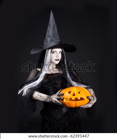 Halloween witch with a carved pumpkin - stock photo