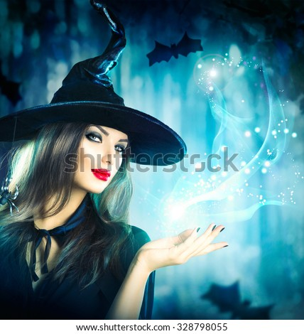 Halloween Witch with a magic in a dark forest. Beautiful young woman in witches hat and costume holding magical light in her hand. Halloween art design