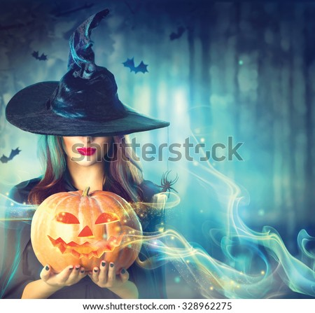Halloween Witch with a magic Pumpkin in a dark forest. Beautiful young woman in witches hat and costume holding carved pumpkin. Halloween art design - stock photo