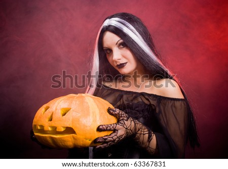 Halloween witch with a pumpkin. Smoke background