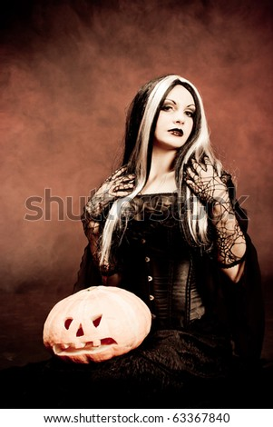 Halloween witch with a pumpkin. Smoke background - stock photo
