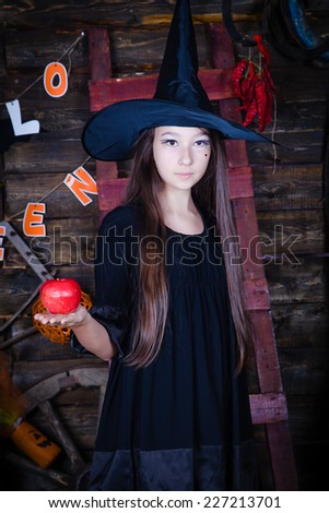 Halloween witch with an apple - stock photo