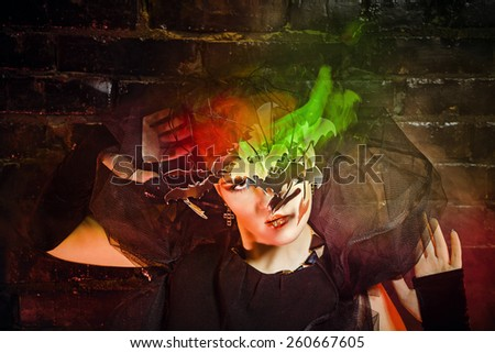 Halloween witch with an unusual makeup and headdress of bats creates magic. Concept for holiday All Saints' Day.
