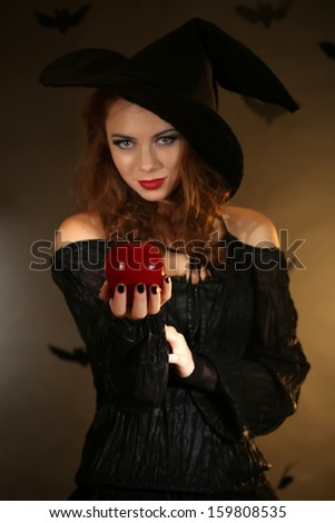 Halloween witch with apple on dark background