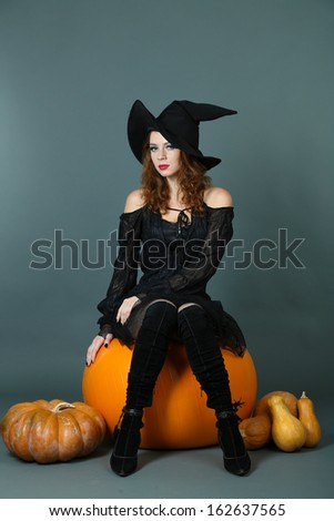 Halloween witch with broom on gray background