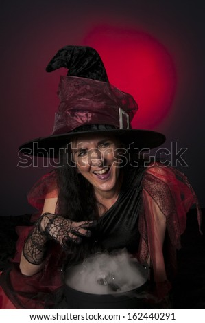 Halloween witch with cauldron, casting spells on dark background