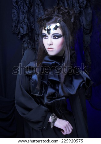 Halloween. Young stylish woman in black dress with artistic visage with smokey-eyes - stock photo