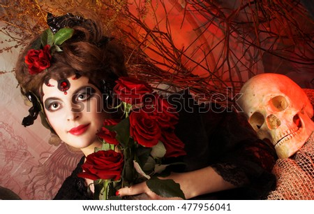 Halloween. Young woman in dramatic artistic image with rose's and skull