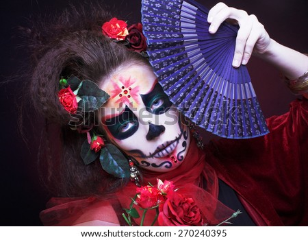 Halloween. Young woman with creative visage and with roses in her hair and with blue fan.