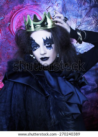 Hallowwen. The Mad queen. Young woman witn creative visage and in crown - stock photo