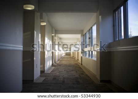 Hallway of apartment building with sun shining through windows