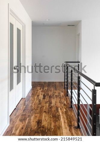 Hallway with Hardwood Floors and Railing in New Home - stock photo