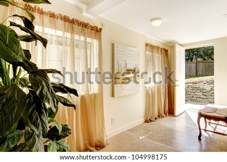 Hallway with two windows and painting and open door to outside. - stock photo
