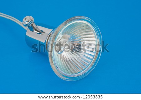halogen lamp with reflector over blue background - stock photo