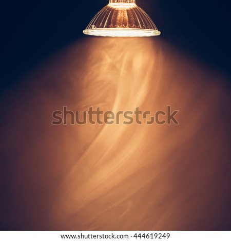 halogen lamp with reflector, warm light in fog - stock photo