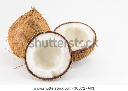 Halved and whole fresh coconuts with coconut leaves on white - stock photo