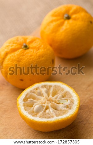 Halved and whole yuzu fruits on a piece a cutting board. Yuzu is a hybrid between Citrus ichangensis and Citrus reticulata, famous for aromatic zest. Formerly know as Citrus junos.  - stock photo