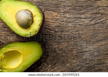 halved avocado on old wooden table - stock photo