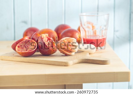 halved blood orange and juicer on kitchen table - stock photo