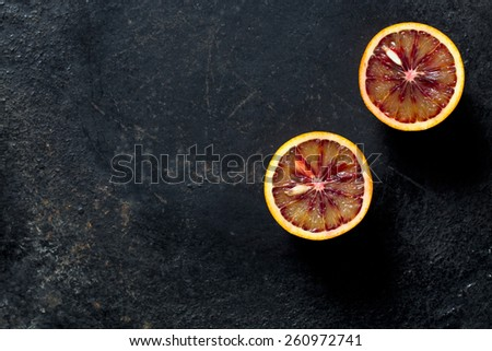 halved blood orange on black background - stock photo
