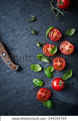Halved cherry tomatoes and basil leaves on black slate - stock photo