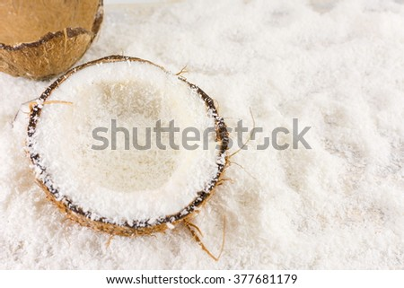 Halved fresh coconut and coconut powder on the table - stock photo