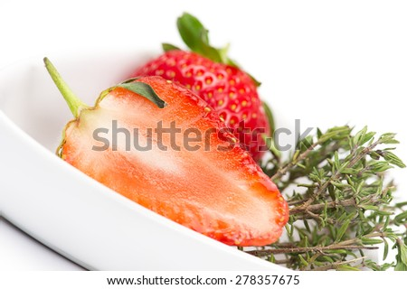 Halved fresh juicy ripe red strawberry showing the structure of the flesh or pulp in a white bowl with a sprig of fresh rosemary to be used as an aromatic flavoring, seasoning and cooking ingredient - stock photo