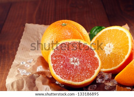Halved fresh orange varieties with the traditional orange coloured pulp and the cara cara orange with its red-pink colouration on crumpled grungy brown paper - stock photo