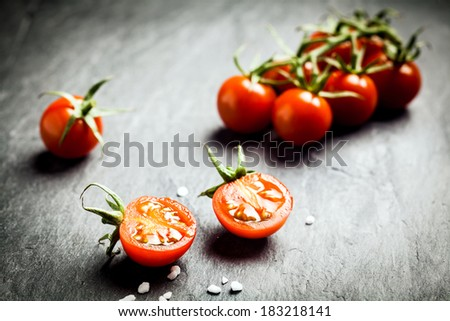 Halved fresh ripe grape tomato showing the pips and juicy pulp in the foreground with a bunch of tomatoes on the vine behind on a dark rustic table, low angle with copyspace - stock photo