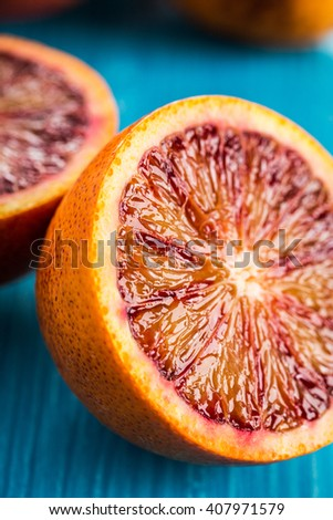 Halves of bright juicy red oranges on blue wooden background