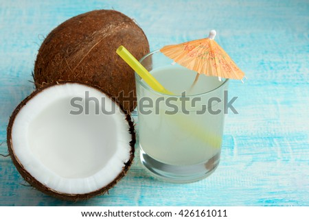 halves of coconut with glass of juice with a cocktail straw on a blue wooden background - stock photo