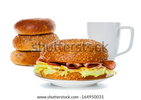 Ham and Cheese Bagel Sandwich With Stacks of Bagel and Coffee Mug in the Background - stock photo