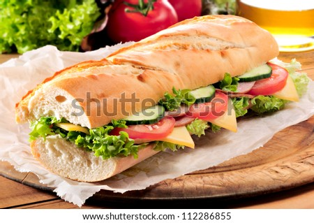 Ham and cheese salad submarine sandwich from fresh baguette. - stock photo