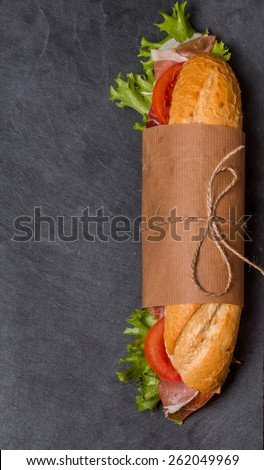 Ham and cheese salad submarine sandwich from fresh baguette on black background - stock photo