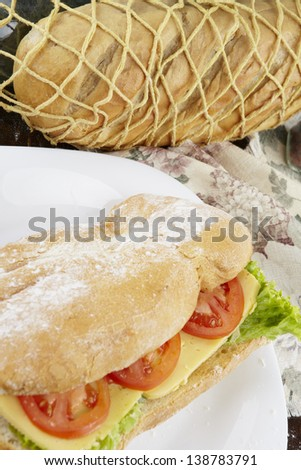 Ham and cheese salad submarine sandwich from freshly cut baguette. - stock photo