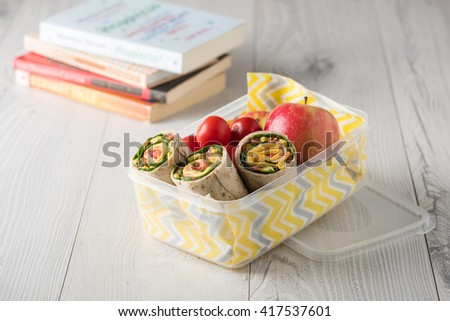 Ham and cheese wraps in lunch box with apple and tomatoes - stock photo