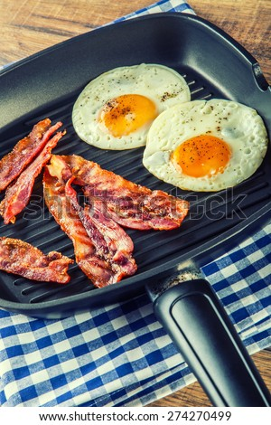 Ham and Egg. Bacon and Egg. Salted egg and sprinkled with black pepper. English breakfast. Grilled bacon, two eggs in a Teflon pan-checked on blue towel on wooden table - stock photo