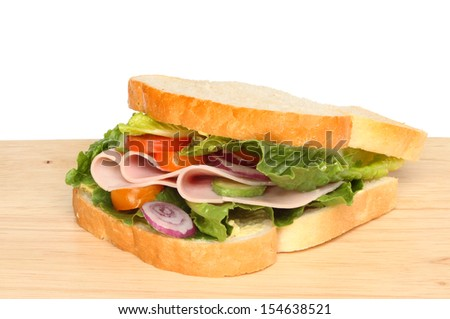 Ham and salad sandwich on a wooden board against a white background