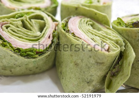 Ham and spinach wraps on a serving platter. Shallow DOF. Focus on wrap on left. - stock photo