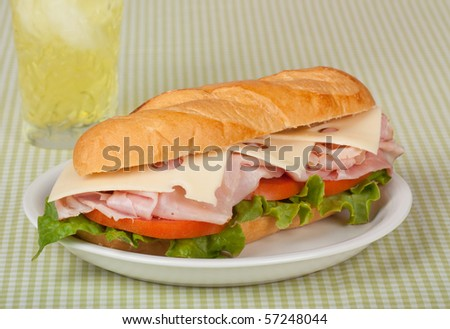 Ham and swiss cheese sub sandwich with lettuce and tomato on a bun with a drink - stock photo