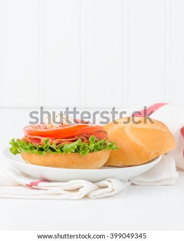 Ham and tomato sandwich on a fresh kaiser bun.  - stock photo