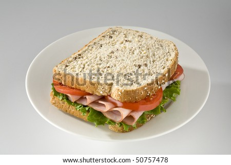 Ham and tomato sandwich on wholegrain bread - stock photo