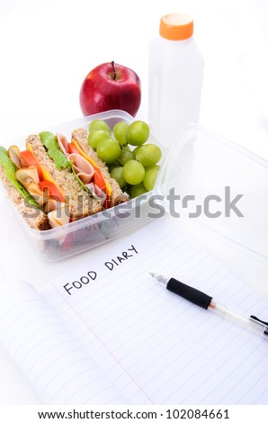 Ham and turkey sandwich with grapes, red apple and water as part of a healthy and well balanced diet and food plan - stock photo