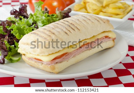 Ham & Cheese Toastie - Cheese, ham and tomato toasted panini served with salad and chips on a red and white gingham background. - stock photo