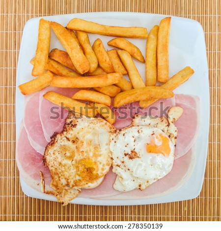 Ham, Fried eggs and chips (fries) on a white plate from above. - stock photo