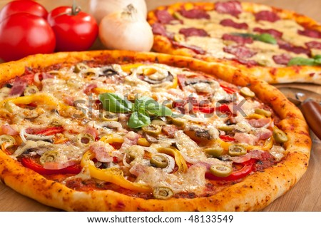 ham, mushroom and vegetable pizza and salami pizza at the back - stock photo