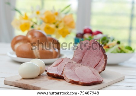 Ham on Easter table with eggs, flowers and decoration - stock photo